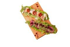 Två smörgåsar med kött på ett träbräde arkivfoto