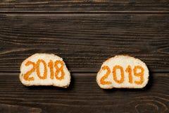 Två smörgåsar med smör en röd kaviar i formen av 2018 och 2019 arkivfoton