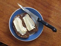 Två smörgåsar med smör på en platta Royaltyfri Bild