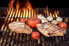 Två smakliga Rib Steaks, tomat, champinjoner som lagas mat över BBQ-galler Arkivfoton