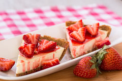 Två smakliga skivor av ostkaka med för snitt jordgubbar upp Arkivfoton