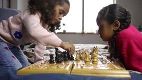 Två smarta små flickor som spelar schack på säng lager videofilmer