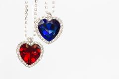 Två smyckenhjärtor blått och rött hänga tillsammans arkivbild