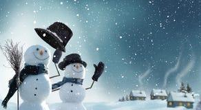 Två snögubbear som står i vinterjullandskap fotografering för bildbyråer
