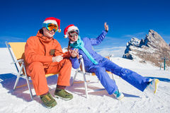 Två snowboarders överst av berget som har roligt sammanträde på stolchaisevardagsrum i santa hattar Fotografering för Bildbyråer