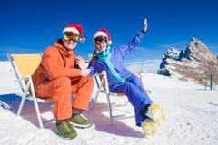 Två snowboarders överst av berget som har roligt sammanträde på stolchaisevardagsrum i santa hattar Arkivbild