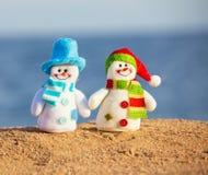 Två snowmans på sand arkivbilder