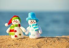 Två snowmans på sand royaltyfri bild