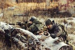 Två soldater i en bakhåll siktar på fienden Royaltyfri Fotografi