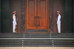 Två soldater i likformig är standindvakten framme av en byggnad i Hanoï (Vietnam) royaltyfri foto