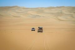Två 4x4 som kör i den namibiska öknen Arkivfoton