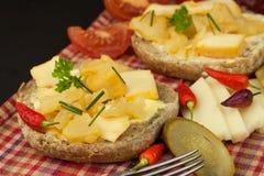 Två sorter av ost på bröd Sund frukost på köksbordet Bröd med tomaten och chili för ost den körsbärsröda Arkivbild