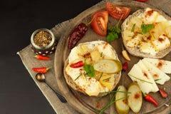 Två sorter av ost på bröd Sund frukost på köksbordet Bröd med tomaten och chili för ost den körsbärsröda Royaltyfria Bilder