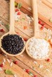 Två sorter av ris i Wood skedar Royaltyfri Fotografi