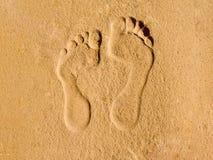 Två spår av mänsklig fot i sandkonsten Royaltyfri Foto