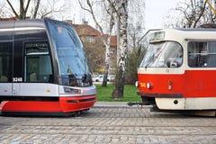 Två spårvagnvagnar med en som mycket är modern, och en som är omodern som en kontrast av nytt och gammalt Royaltyfri Bild