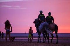 Två spanska poliser som patrullerar stranden på solnedgången på hästrygg Arkivfoton