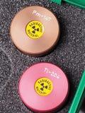 Två specialistbehållare med varningsklistermärken och gravyr som innehåller radioaktiva isotoper Royaltyfri Fotografi