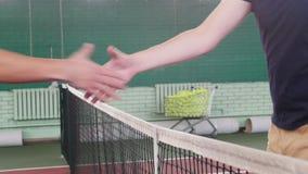 Två spelare för unga män på tennisbanan kommer närmare rastret och skakahänder arkivfilmer