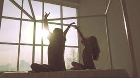 Två spensliga kvinnor som gör yoga mot fönsterbakgrund arkivfilmer