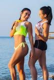 Två sportflickor på en strand royaltyfri bild