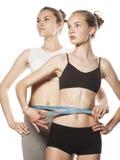 Två sportflickor som mäter sig, isolerade på arkivfoto