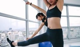 Två sportiga flickor som gör sträckning arkivfoton