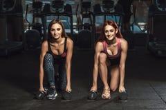 Två sportiga unga flickor för härlig kondition som gör utfall med hantlar i idrottshall Arkivbild
