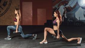Två sportiga unga flickor för härlig kondition som gör utfall med hantlar i idrottshall Royaltyfria Bilder