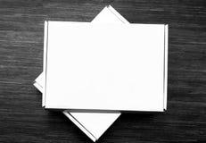 Två stängda vita lådaaskar som isoleras på mörk träbakgrund arkivbild