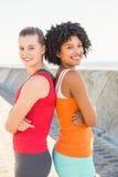 Två stående le unga kvinnor tillbaka att dra tillbaka Fotografering för Bildbyråer