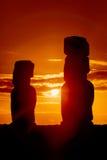 Två stående moais i röd solnedgång Fotografering för Bildbyråer