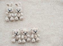 Två stack vita kaniner och tre björnar royaltyfri bild