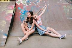 Två stads- tonåriga flickor som poserar i skridsko, parkerar arkivbild