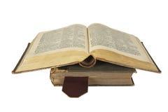 Två staplade antika sjaskiga böcker med öppnat upp på en överkant Arkivfoton