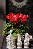 Två statyetter av änglar och röda blommor Arkivbilder