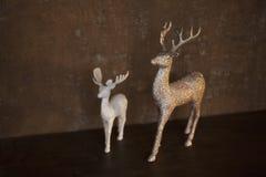 Två statyetter av hjortar - liten vit och stor guld- färg - ställning på en brun tabell arkivbild