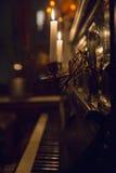 Två stearinljus i ljusstakar som fästas till väggen av det svarta pianot Royaltyfri Foto
