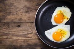 Två steka ägg i panna på tabellen Royaltyfri Foto
