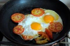 Två stekte ägg i svart stekpanna och skivar tomaten Process av matlagning royaltyfri fotografi