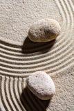 Två stenar över sand fodrar för begrepp av andlighet arkivfoton