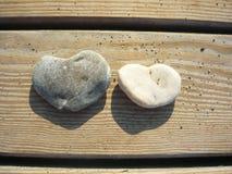 Två stenar i form av hjärtor på en träbakgrund arkivfoto