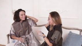 Två stilfulla flickavänner möter sig i en slags tvåsittssoffa gör mellanslag inomhus, med vita väggar på backgroungen Flickor som stock video