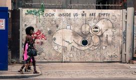 Två stilfulla hipsterflickor som går av en vägg, dekorerade framme med en grafitti Arkivfoton