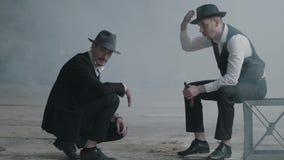 Två stilfulla män i hattar, en som sitter på stolen, andra som squatting i en övergiven byggnad Maffiagrabbarna har stock video
