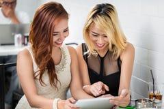 Två stilfulla unga kvinnor som surfar det netto Fotografering för Bildbyråer