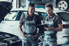 Två stiliga lyckliga auto Mecanics i garage arkivfoto