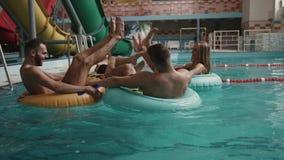 Två stiliga lyckliga charmiga kvinnor för manadn två har gyckel i det lyxiga hotellet De simmar på uppblåsbar stock video