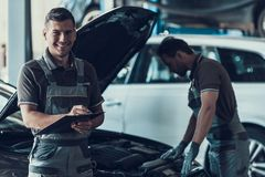 Två stiliga Mecanics som reparerar bilen i garage royaltyfria bilder
