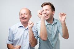 Två stiliga vänner som dansar på födelsedagpartiet Sonen och fadern är så lyckliga dem segrade i lotteri royaltyfri fotografi